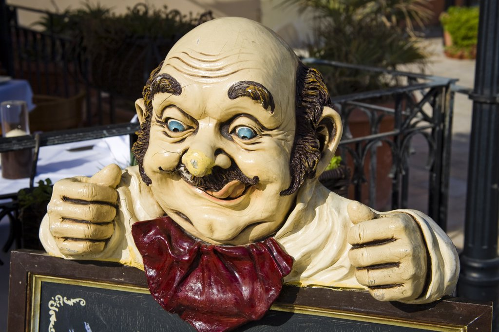 Carving of a man licking his lips above a menu board outside a restaurant, Saint Julian's, Malta : Stock Photo