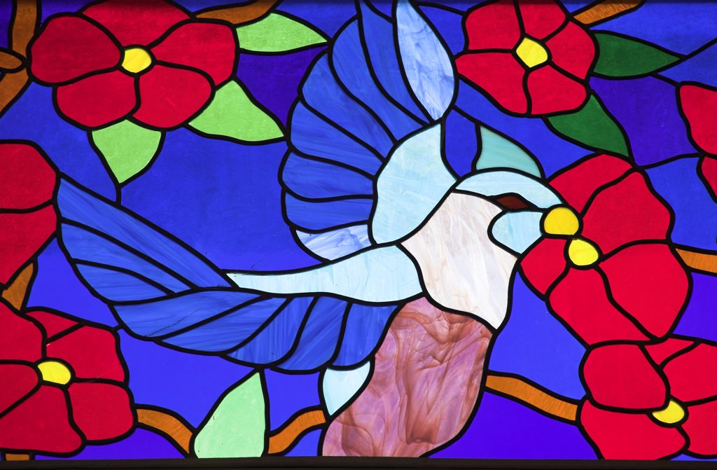 Colourful stained glass window of a bird perched in a tree, Trinidad, Cuba : Stock Photo