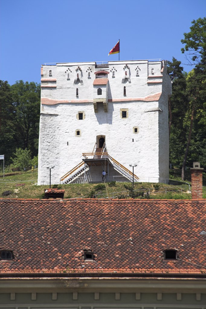 A white watchtower on hillside, overlooking town square, Brasov, Transylvania, Romania : Stock Photo