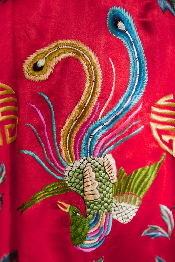 Colourful red Chinese embroidered silk garment depicting a phoenix bird, for sale, China : Stock Photo