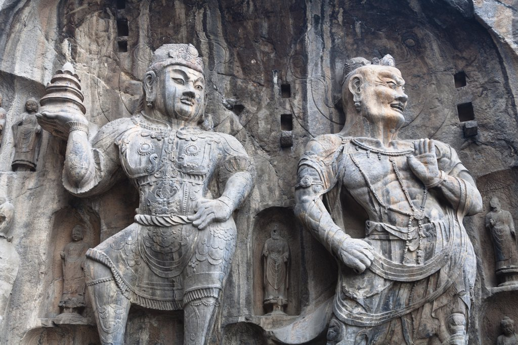 Carved statues, Fengxian Temple, Longmen Grottoes and Caves, Luoyang, Henan Province, China. Tang Dynasty : Stock Photo
