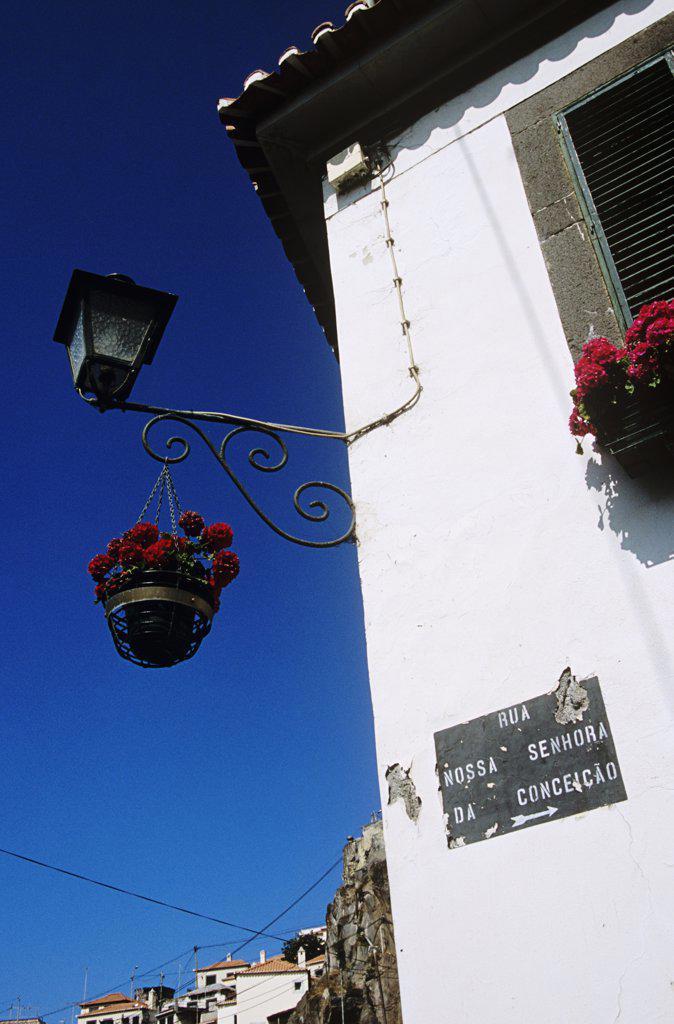 Street light and hanging basket, Rua Nossa Senhora Da Conceicao, Camara de Lobos, Madeira : Stock Photo