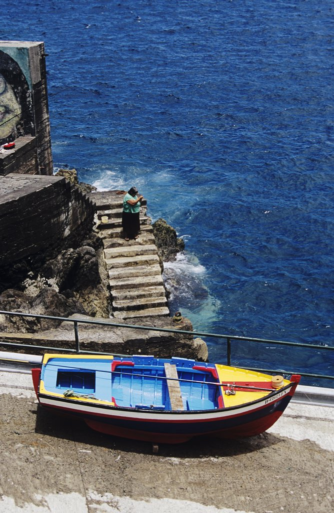 Stock Photo: 4290-5702 Colourful painted fishing boat on slipway, and lady fishing, Porto Do Moniz, Madeira