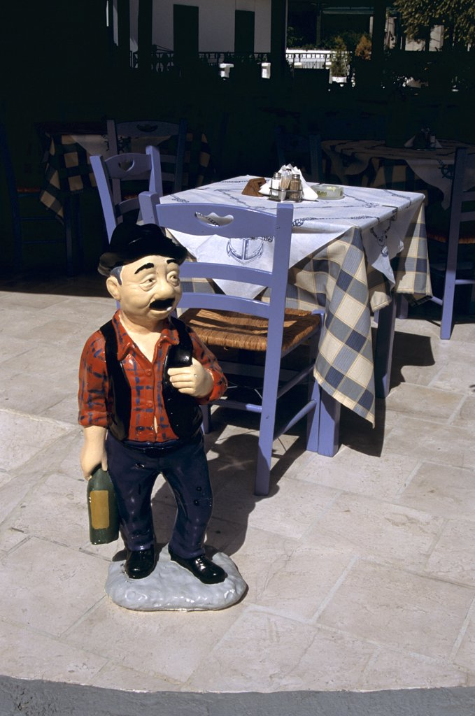 Stock Photo: 4290-6921 Model of a waiter in front of table and chairs outside a restaurant, Agia Efimia, Kefalonia, Greece