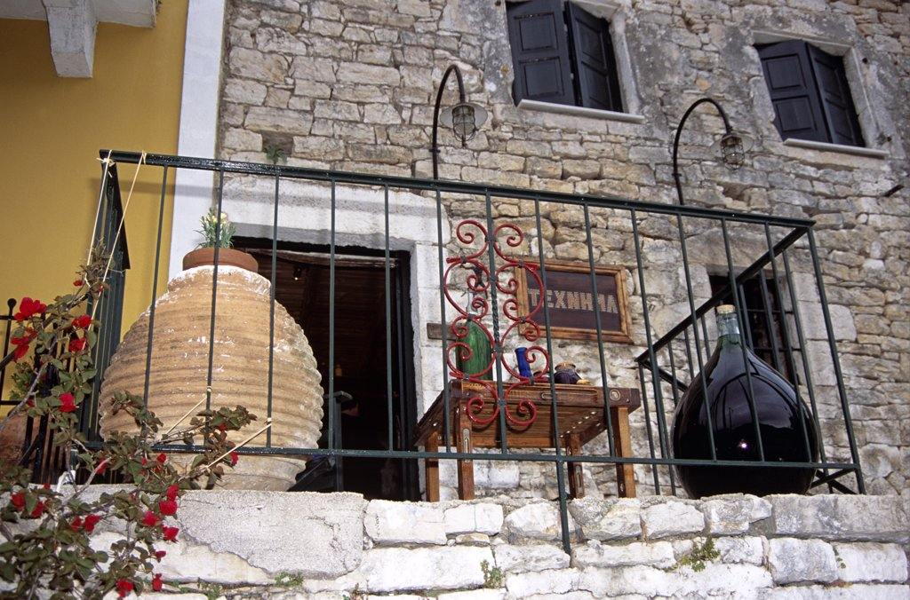 Stock Photo: 4290-7021 Pot, table and demijohn on balcony, Texnhma gift shop, Kioni, Ithaca, Greece