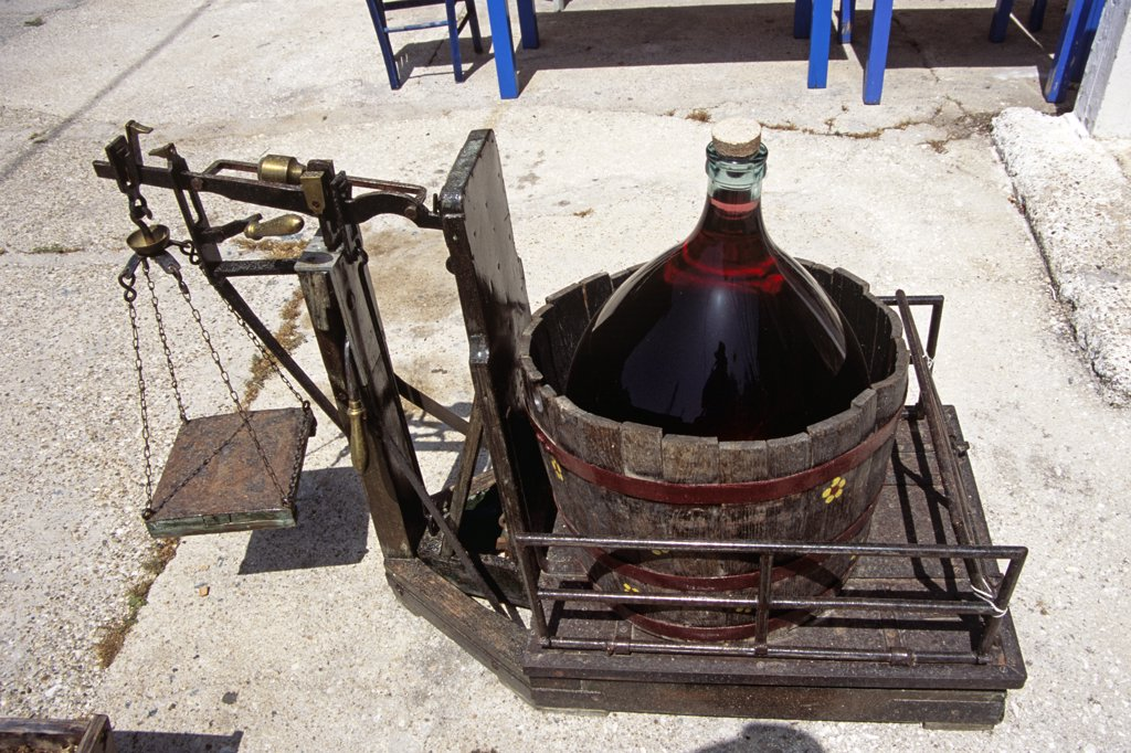 Stock Photo: 4290-7022 Demijohn containing red liquid in barrel, old scales, outside Texnhma gift shop, Kioni, Ithaca, Greece