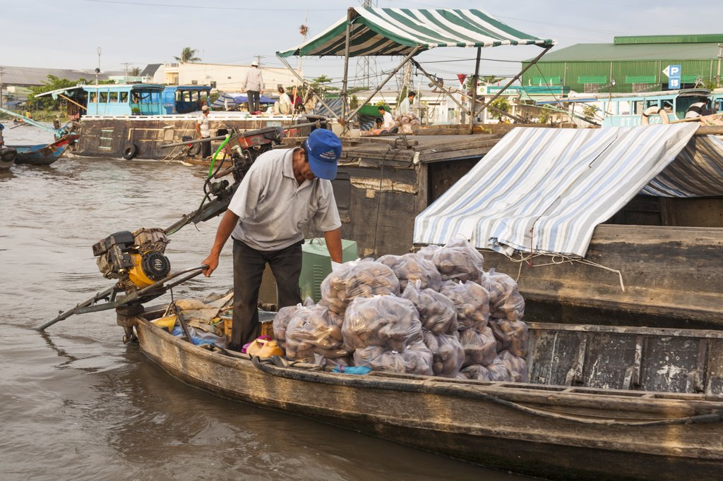 Stock Photo: 4290-9250 Vietnam, Mekong River Delta, Cai Rang, near Can Tho, man selling vegetables from boat in floating market