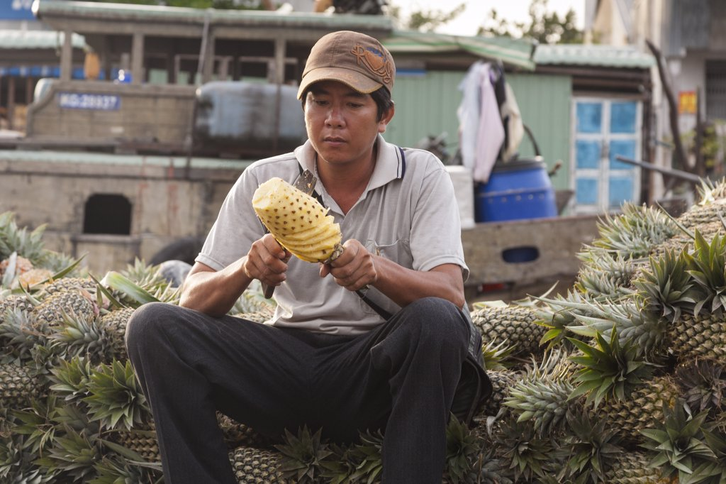 Stock Photo: 4290-9259 Vietnam, Mekong River Delta, Cai Rang, near Can Tho, man cutting pineapple in floating market