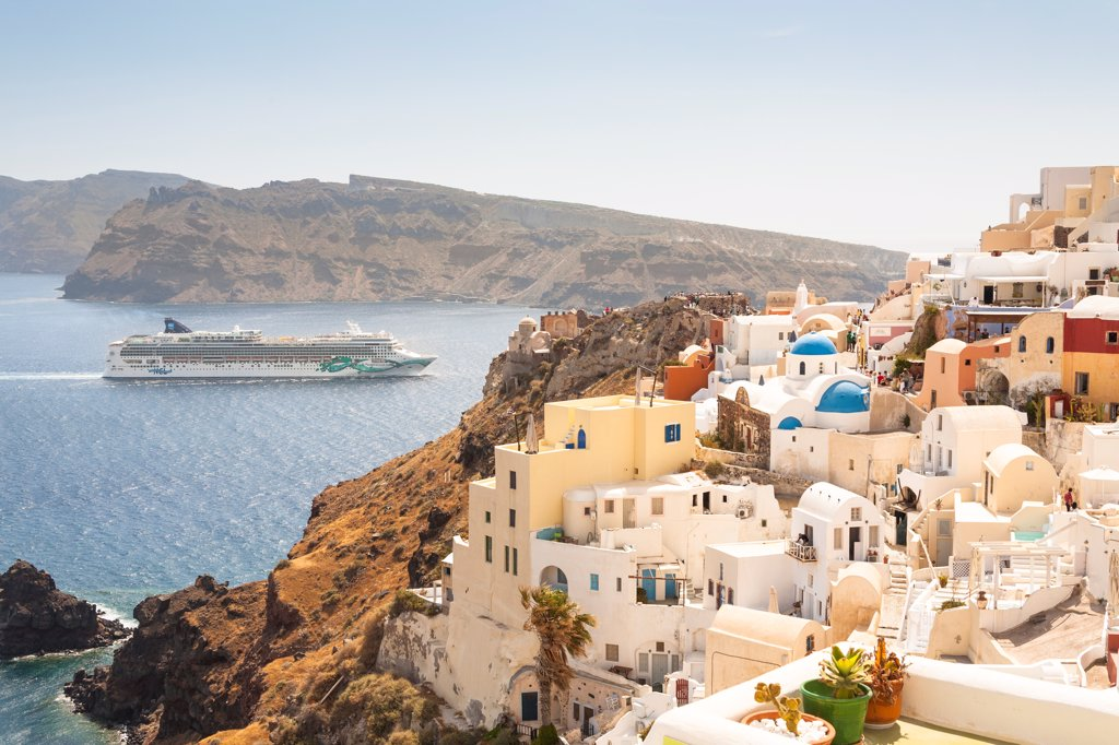 View of waterside clifftop buildings and the Norwegian Jade cruise ship, Oia, Santorini, Greece : Stock Photo
