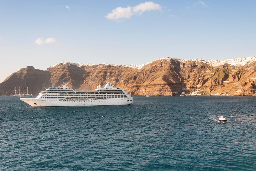 Stock Photo: 4290-9570 Clifftop towns of Oia on left, Fira on right, Skala port below, and Nautica cruise ship, Santorini, Greece