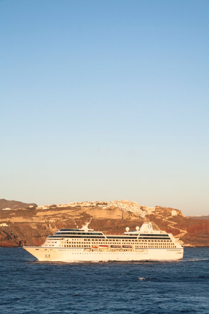 Stock Photo: 4290-9575 Nautica cruise ship passing the clifftop village of Oia, Santorini, Greece