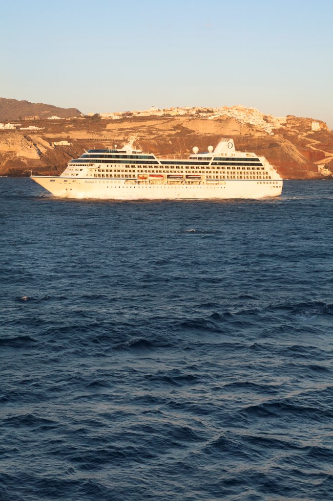 Nautica cruise ship passing the clifftop village of Oia, Santorini, Greece : Stock Photo