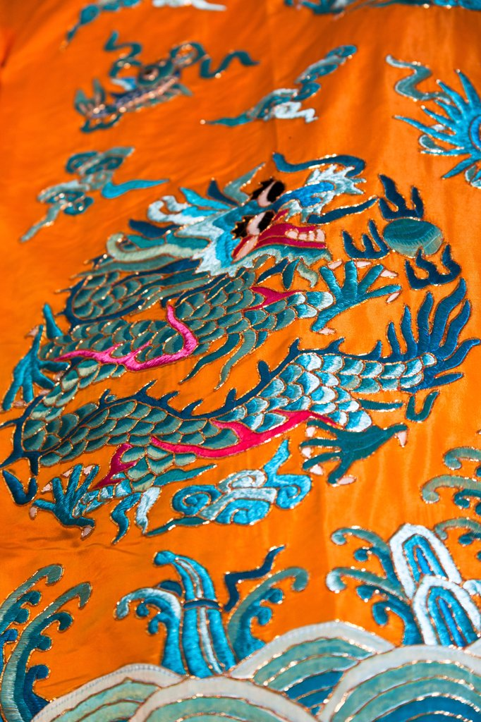 Colourful orange and blue Chinese embroidered silk garment for sale, China : Stock Photo