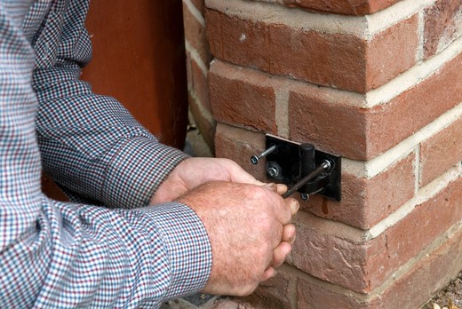Stock Photo: 4291-10517 Blacksmith fixing bracket to brickwork using strong screws prior to hanging finished gate on it's hinges