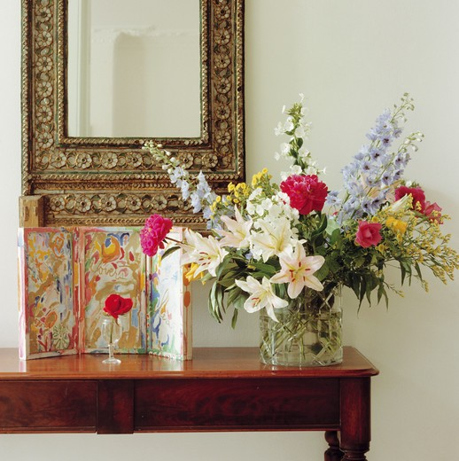 Stock Photo: 4291-1059 Close-up of small picture and summer flowers in informal arrangement in glass vase on table below ornate mirror
