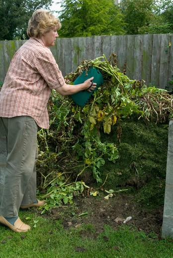 Woman adding organic material to compost heap : Stock Photo
