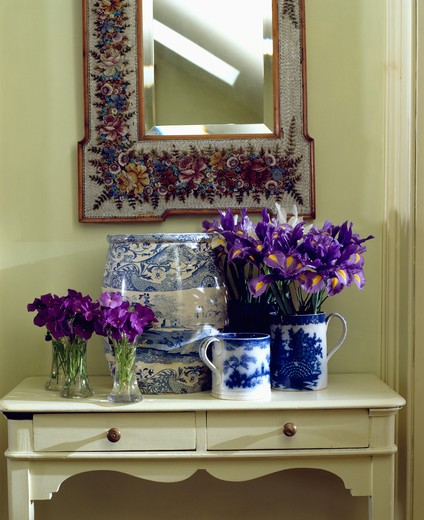 Close-up of purple pansies in glass vases and blue irises in blue and white jug on cream console table below floral mirror : Stock Photo