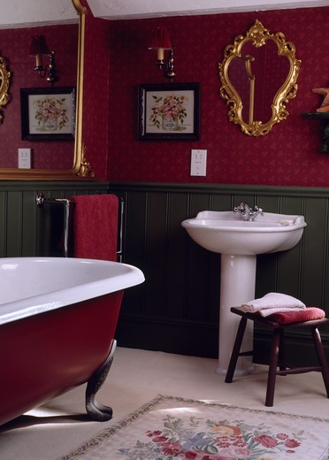 Stock Photo: 4291-11039 Ornate gilt mirror above white pedestal basin in red bathroom with green dado panelling and central rolltop bath