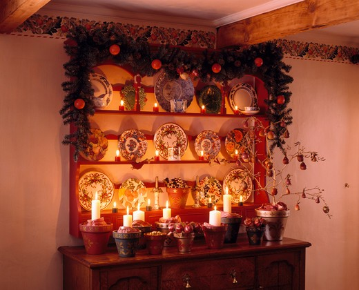 Stock Photo: 4291-11144 Christmas garland on shelves above sideboard with lighted candles