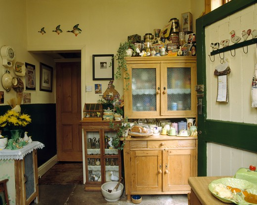 Stock Photo: 4291-11277 Fifties dresser piled with crockery in cluttered kitchen with flying ducks over doorway