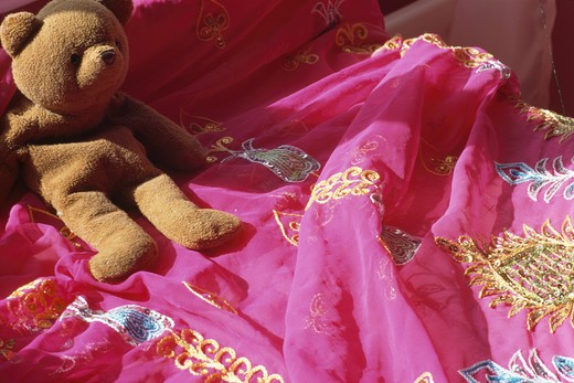 Close-up of teddybear on embroidered pink Indian bedcover : Stock Photo