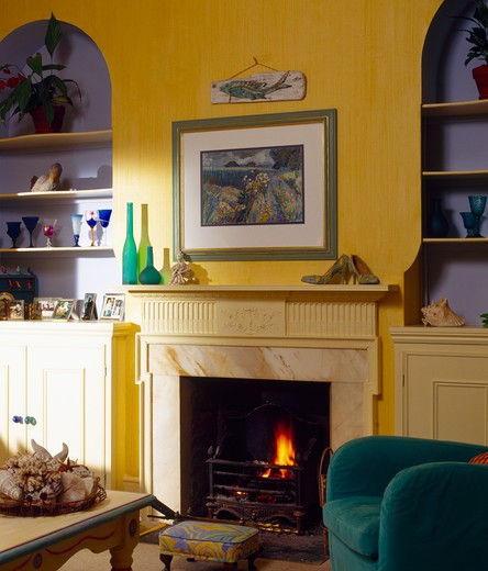 Picture above fireplace in yellow living room with blue alcoves : Stock Photo