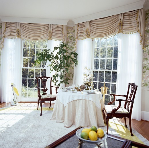 Beige ruched blinds and white curtains at tall windows in eighties diningroom with beige cloth on circular table : Stock Photo