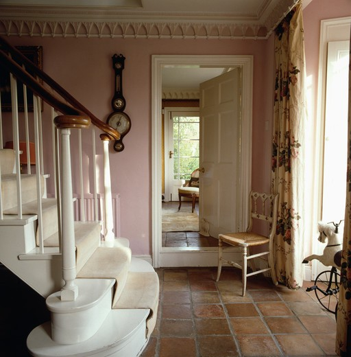 Stock Photo: 4291-12538 Gothic cornice and small Gothic chair in pink country hall with terracotta tiled floor and white staircase