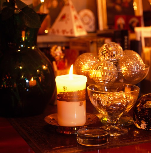 Stock Photo: 4291-13720 Close-up of candles and gold Christmas baubles on dining table
