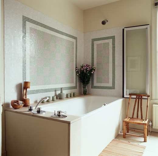 Stock Photo: 4291-13744 Mosaic tiled wall above bath in traditional bathroom with bamboo chair in front of folding glass panel