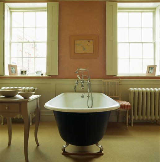 Stock Photo: 4291-13775 Rolltop bath in the centre on pink and cream townhouse bathroom