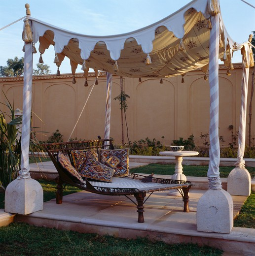 Stock Photo: 4291-13901 Embroidered Rajastani cushions on charpoy below tented canopy in courtyard of Rajvilas Hotel in Rajastan