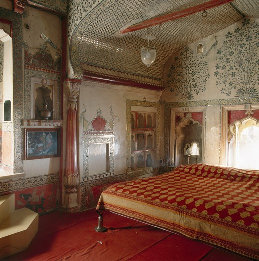 Stock Photo: 4291-13957 Red and yellow Indian bedcover on bed in Rajastani bedroom with floral mosaic tiled walls and ceiling