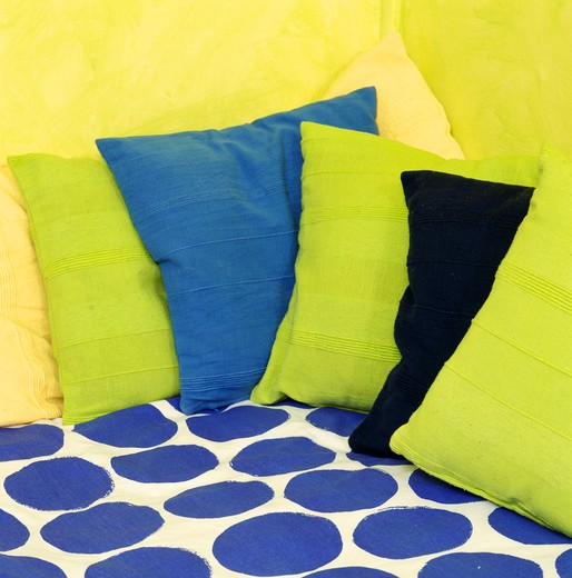 Close-up of lime-green and blue cushions on blue spotted fabric : Stock Photo