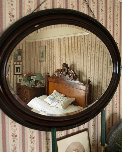 Stock Photo: 4291-15507 Close-up of oval mahogany-framed mirror with reflection of old-fashioned country bedroom