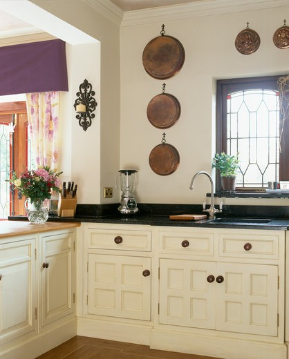 Stock Photo: 4291-15754 Copper pans on wall above cream fitted units in traditional country kitchen
