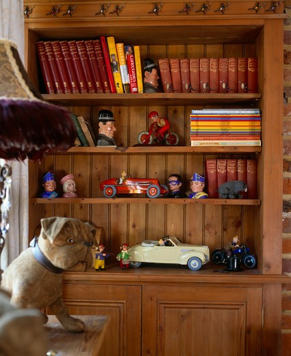 Collection of old toys on bookshelves in study with large toy dog : Stock Photo