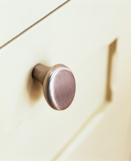 Close-up of brushed steel handle on cream drawers : Stock Photo