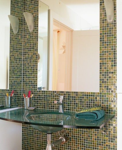 Stock Photo: 4291-16068 Close-up of large mirror above glass basin in modern bathroom with green and gold metallic mosaic tiles
