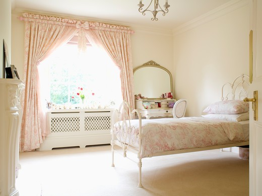 Pink Toile-de-Jouy curtains and bedlinen in cream country bedroom with cream carpet and wrought-iron bed : Stock Photo