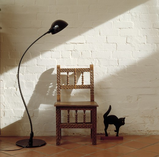 Black floor lamp and carved wooden chair against white painted brick wall : Stock Photo