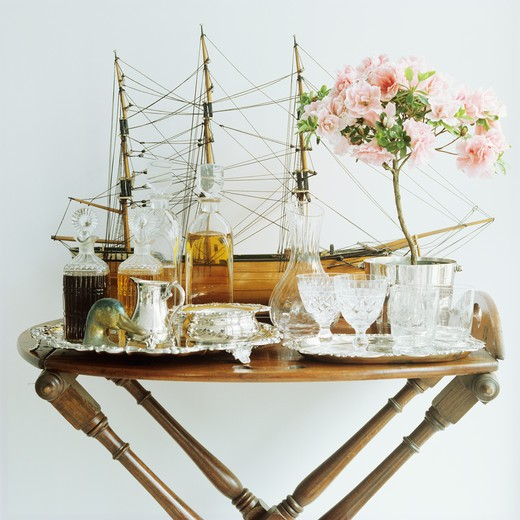 Stock Photo: 4291-16727 Collection of antique glasses and decanters with model sailing ship on antique table