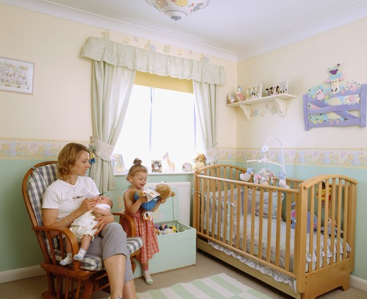 Mother and baby with toddler in childs nursery bedroom with wooden cot : Stock Photo