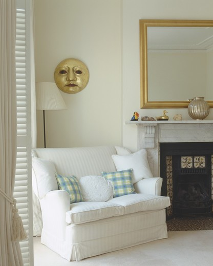 White and checked cushions on small white sofa beside fireplace in white living room with gilt sun sculpture on wall : Stock Photo