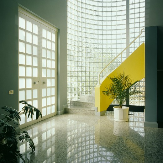 Stock Photo: 4291-18112 Curved glass brick wall and yellow staircase in modern hall with polished pale grey flooring and double glazed doors
