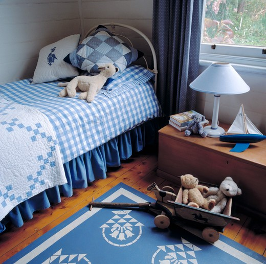 Stock Photo: 4291-18117 Patchwork cushions and quilt on bed with blue checked duvet in child's bedroom with blue rug and vintage toys