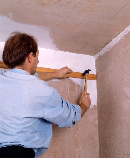 Stock Photo: 4291-1815 Man attaching wooden picture rail to wall before fitted renovated plaster cornice