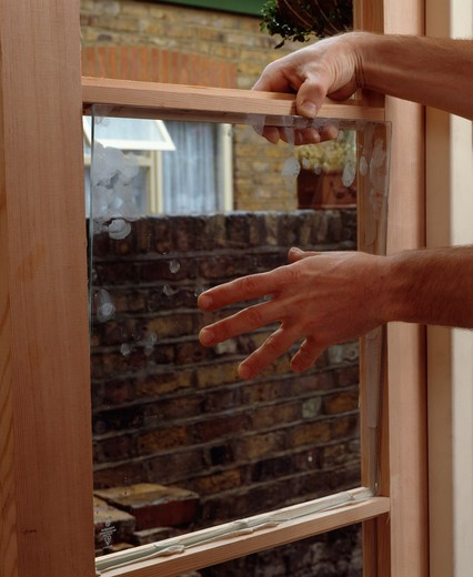Close-up of hands replacing sash window : Stock Photo
