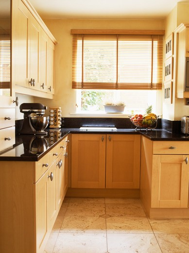 Pale wood fitted units in small modern kitchen with cane blind on window : Stock Photo