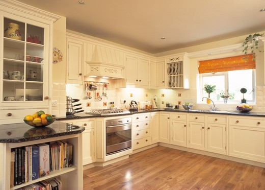 Stock Photo: 4291-1849 Cream fitted cupboards with black granite worktops in contemporary kitchen with wooden floor